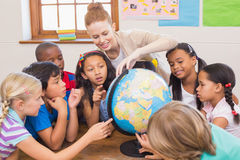 Cute pupils and teacher in classroom with globe Stock Images