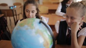 Schoolgirl in geography class studying the countries and continents with the globe. Cute pupils and teacher in classroom with globe at the elementary school stock video footage