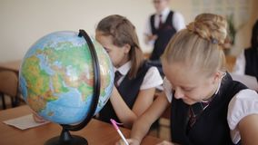 Cute pupils and teacher in classroom with globe at the elementary school. Students in the class in geography class learn to work with the globe stock footage