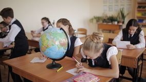 Students in the class in geography class learn to work with the globe. Cute pupils and teacher in classroom with globe at the elementary school stock video