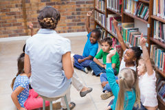 Cute pupils and teacher having class in library Royalty Free Stock Photos