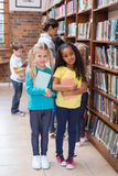 Cute pupils and teacher looking for books in library Royalty Free Stock Images