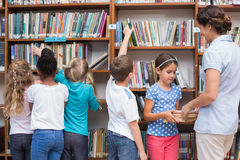 Cute pupils and teacher looking for books in library Stock Photography