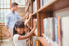 Cute pupils and teacher looking for books in library stock image