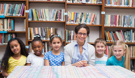 Cute pupils and teacher looking at camera in library Royalty Free Stock Images