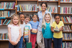 Cute pupils and teacher looking at camera in library Stock Photography