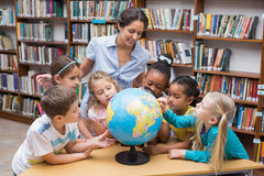 Cute pupils and teacher looking at globe in library Royalty Free Stock Photos