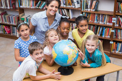 Cute pupils and teacher looking at globe in library Royalty Free Stock Photo