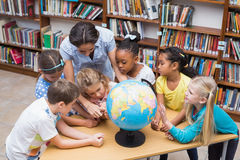 Cute pupils and teacher looking at globe in library Royalty Free Stock Image