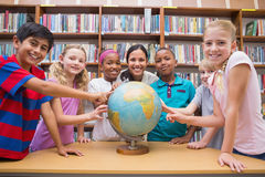 Cute pupils and teacher looking at globe in library Stock Photos