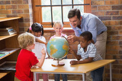 Cute pupils and teacher looking at globe in library Stock Images