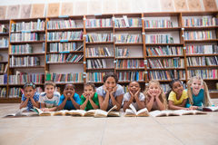 Cute pupils and teacher lying on floor in library Stock Photos