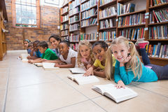 Cute pupils and teacher lying on floor in library Royalty Free Stock Photo