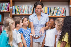Cute pupils and teacher reading book in library Stock Photography