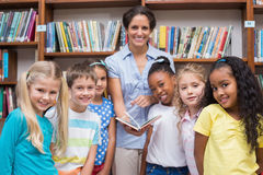 Cute pupils and teacher reading book in library Royalty Free Stock Photo