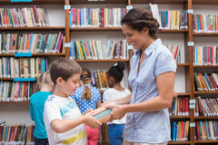 Cute pupils and teacher reading book in library Stock Photo