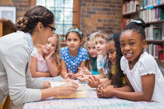 Cute pupils and teacher reading in library Stock Photos
