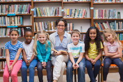 Cute pupils and teacher reading in library Royalty Free Stock Image