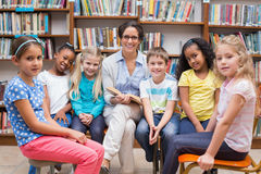 Cute pupils and teacher reading in library Royalty Free Stock Photography