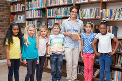 Cute pupils and teacher reading in library Royalty Free Stock Photo
