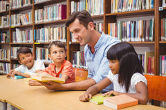 Cute pupils and teacher reading in library Stock Image