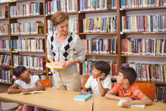 Cute pupils and teacher reading in library Royalty Free Stock Photos