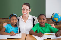 Cute pupils and teacher smiling at camera in classroom Royalty Free Stock Photos