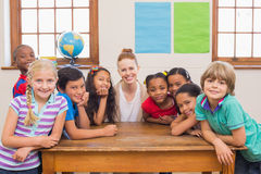 Cute pupils and teacher smiling at camera in classroom Stock Photography