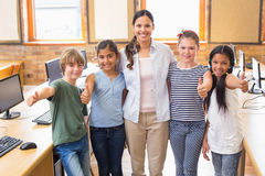 Cute pupils and teacher smiling at camera in computer class Royalty Free Stock Photos