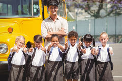 Cute pupils with their school bus driver Stock Image