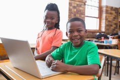Cute pupils using laptop in classroom Stock Images