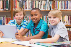 Cute pupils using tablet computer in library Royalty Free Stock Photography