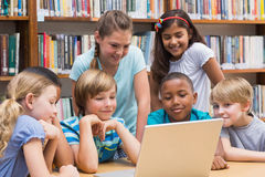 Cute pupils using tablet computer in library Stock Photo