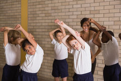 Cute pupils warming up in PE uniform Stock Images
