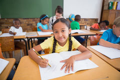 Cute pupils writing at desk in classroom Stock Photography