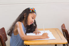 Cute pupils writing at desk in classroom Royalty Free Stock Image