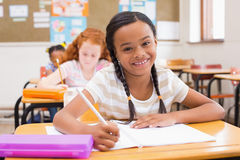 Cute pupils writing at desk in classroom Stock Image