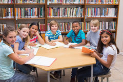 Cute pupils writing at desk in library Royalty Free Stock Photos