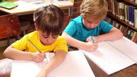 Cute pupils writing in library. At the elementary school stock video footage
