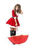Cute puzzled Santa girl with umbrella and scratching head looking down. Stock Image