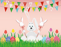 Cute rabbit with easter bunnies on a stick with red bows. The hare sits. On a grass background of a garland of multi-colored flags. Invitation to a holiday Stock Photos