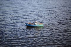 Cute radio controlled blue toy boat on water surface. Hobby concept. royalty free stock photo