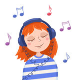 Cute red girl listens to music Royalty Free Stock Photos