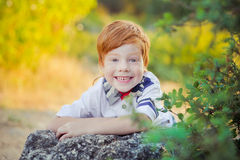 Cute red hair boy smiling to camera and standing in forest with horse Stock Images