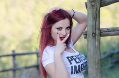 Cute red hair lady outside. Sweet red hair lady outside, bold red lips white short shirt standing against wooden fence making peace symbol as she look at the Stock Image
