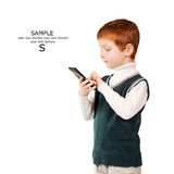 Cute red haired child stands looking at the smartphone. Isolated Stock Photography