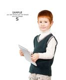 Cute red haired child stands with a tablet PC. Isolated at the w Royalty Free Stock Image