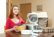 Cute red haired female with electric crock pot in her kitchen in Royalty Free Stock Photography