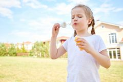 Cute Red Haired Girl Blowing Bubbles royalty free stock image