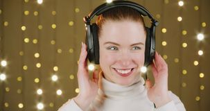 Listening to music. Cute red-haired girl enjoying listening to music with headphones. Studio video stock video